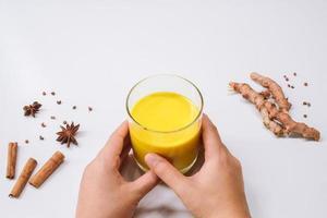 manos sosteniendo leche dorada cúrcuma latte