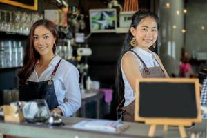 Female Asian baristas smiling behind coffee shop counter