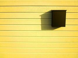Dark brown mailbox on bright yellow wooden wall