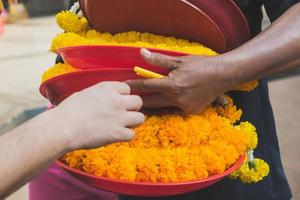 Seller's hand picking a tray of fresh marigold garland photo