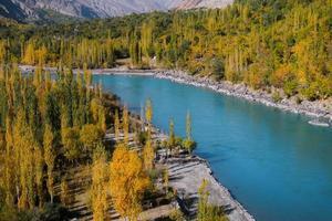 río ghizer que fluye a través del bosque en otoño