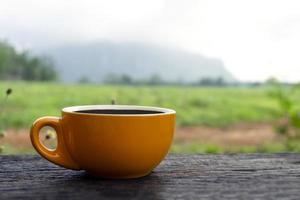 Cup of coffee on table in scenic outdoor setting