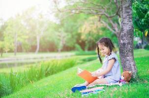 Young Asian girl reading book in a park