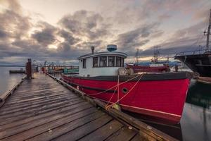 Red and white boat on dock under cloudy sky photo