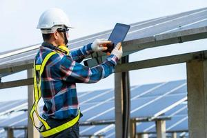 Man wearing safety equipment next to solar panels