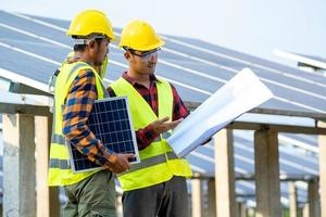 Men wearing safety equipment next to solar panels photo