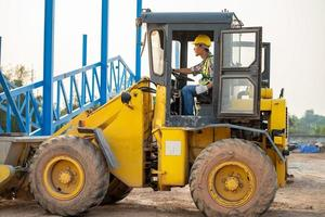 Construction worker driving backhoe loader