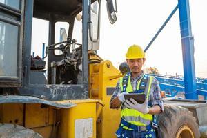Trabajador de la construcción junto a la retroexcavadora