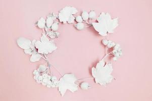 Círculo de bayas blancas y hojas blancas sobre fondo rosa