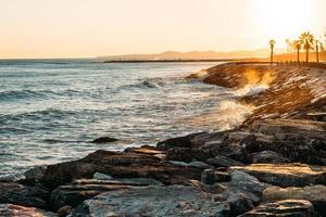 Waves splashing on rocky beach during golden hour photo