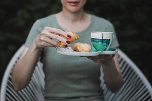 mujer sosteniendo la bandeja con pasteles y taza de café