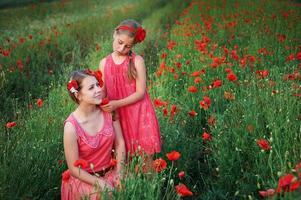 Two girls in pink dresses in poppy field