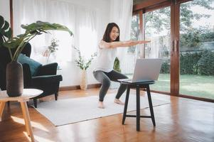 Woman learning online workout excercise class at home from laptop