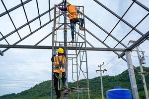 Construction workers wearing safety harnesses on scaffolds