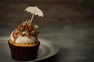 Cupcake topped with icing, almonds, and caramel