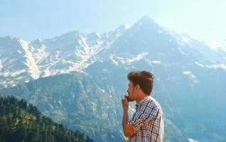Man in plaid looking at mountains and trees