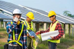 Men wearing safety equipment next to solar panels