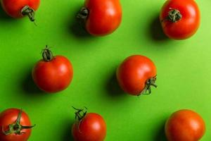 Ripe tomatoes on green background