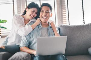 Happy Asian couple having a good time at home photo