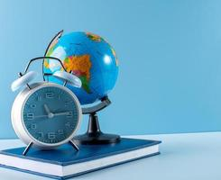 Globe, alarm clock and notebook on blue background