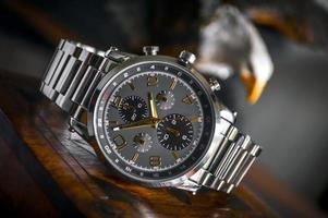 Silver linked bracelet and black round chronograph watch