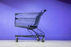 Shopping cart in front of purple wall