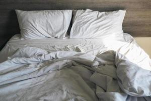Unmade bed with gray comforter and white sheets