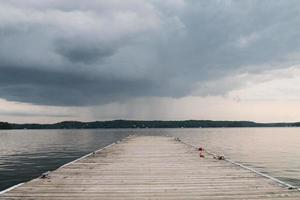 Wooden dock on body of water under cloudy sky
