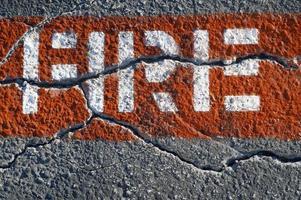 Pintura de carril de incendios sobre pavimento agrietado