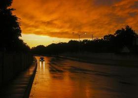 Auto auf der Straße unter orange bewölktem Himmel