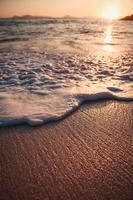 Foamy water on sand at beach photo