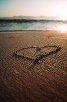 Heart drawn in sand at beach by water