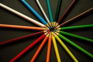 Colorful pencils touching tips forming wheel