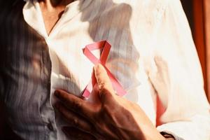 Woman pointing at pink ribbon on her shirt