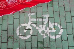 Bike road sign painted on green bricks