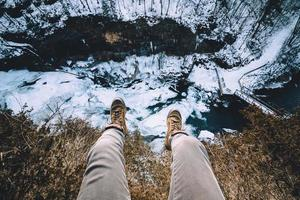 Person hanging legs on cliff over frozen river