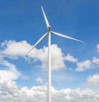 desde detrás de la turbina eólica en el hermoso cielo azul nublado. foto