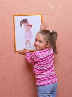 Smiling girl hanging up a self portrait photo