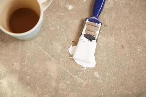 Taza de café y pincel en el piso