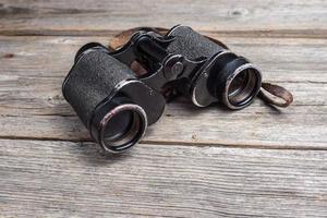 vintage binoculars on wooden background photo