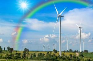 Wind turbine power generator with rainbow on blue sky