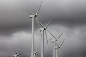 wind energy windmills in a dark storm, electric generators photo