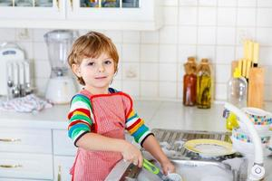 Funny kid boy helping and washing dishes at home photo