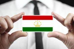 Businessman holding a business card with Tajikistan Flag