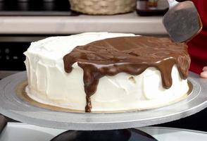 El chocolate derretido se extiende sobre el pastel de crema.