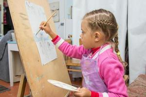 Five-year girl is engaged in drawing in the artists studio