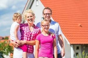 familia de pie orgullosa frente a casa foto