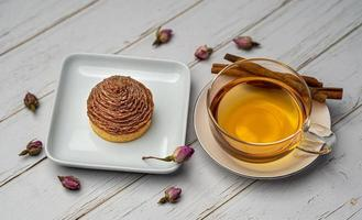 Cupcake on white ceramic plate and cup of tea with cinnamon