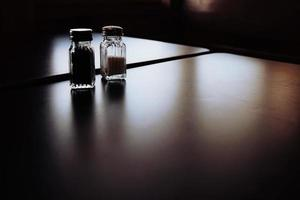 Salt and pepper jars on table