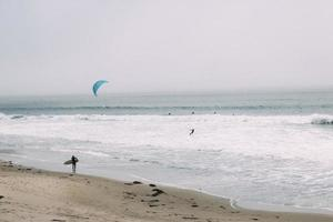 Surfer on beach and parasailer in water photo
